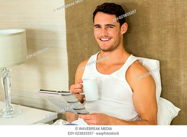 Young man reading newspaper while holding a cup of tea