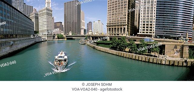 This is a tour boat on the Chicago River during summer. The Chicago Tribune Building, Chicago Sun Times Building, and the IBM Building surround the river