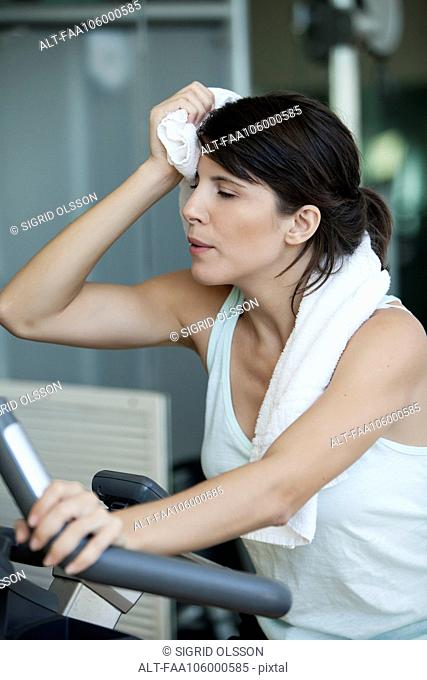 Woman working out in gym, wiping her brow with a towel