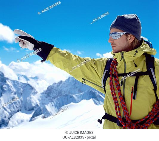 Male hiker pointing on snowy mountain