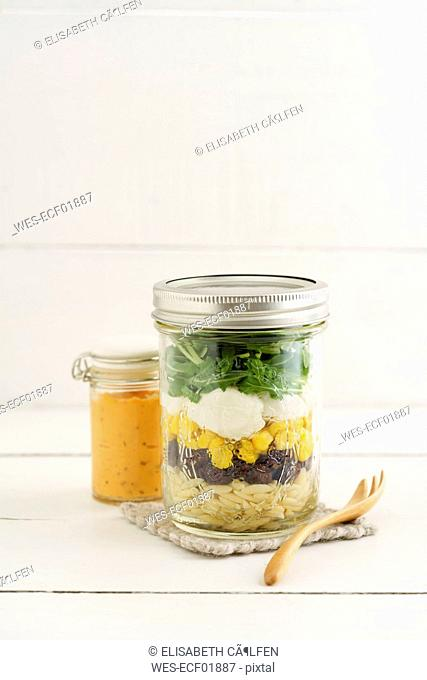 Jar of vegetarian mixed salad with Kritharaki, corn, rocket and cranberries and jar of cocktail sauce
