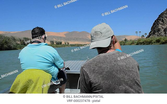 Namibia Africa three tourists riding boat on Kunene River Serra Cafema Camp resort looking at Angola across river in safari vacation border of Namibia and...
