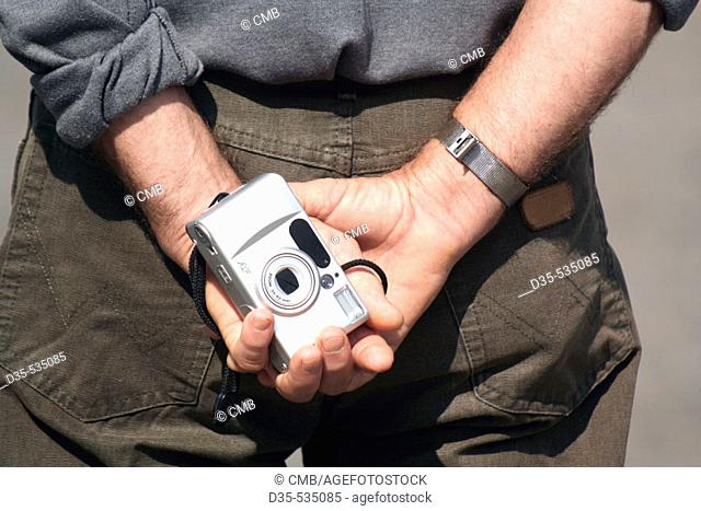 Tourist holding camera in his hands