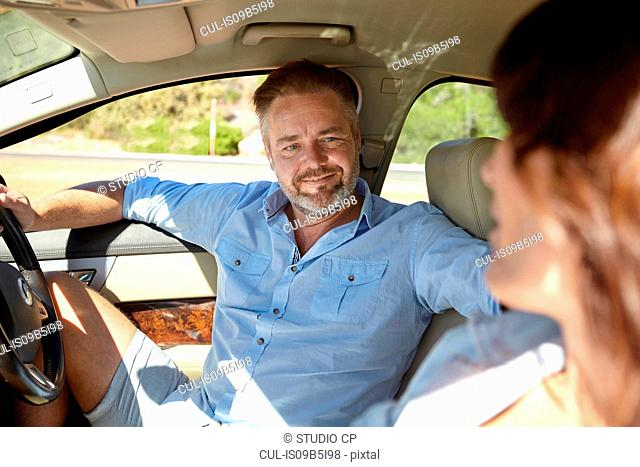 Couple in car, man in driver's seat, sitting facing woman