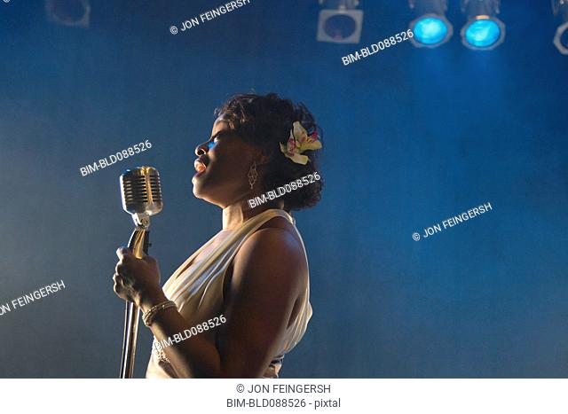 Black woman singing on stage