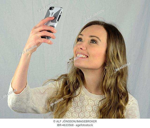 Young woman make a selfie with a mobil phone, smile