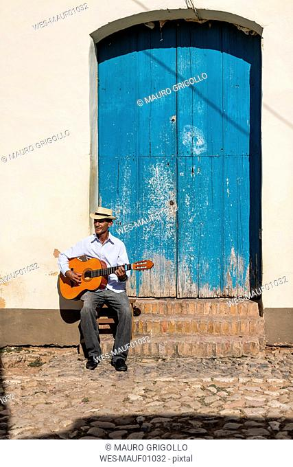 Cuba, man playing guitar on the street
