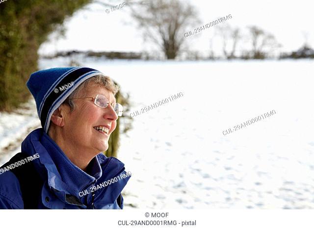 Happy retired woman in a snow field