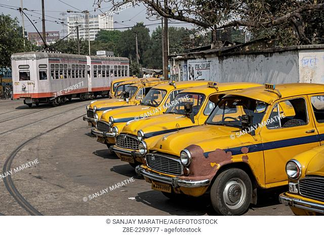 Yellow Ambassador taxis and a tram at BBD Bagh (Dalhousie square) in Kolkata (Calcutta), West Bengal, India. Started by the Calcutta Tramways Company on 24...