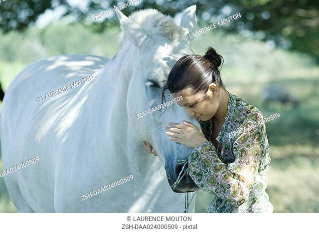 Young woman leaning her head against horse