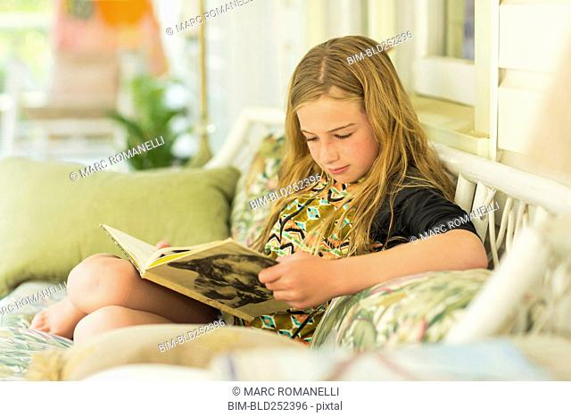 Caucasian girl reading book on sofa