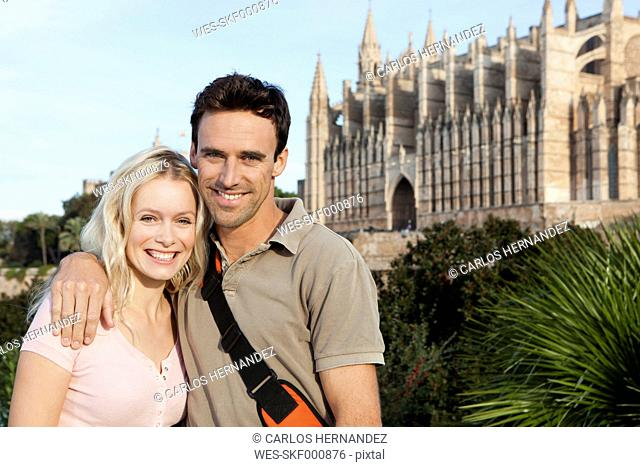 Spain, Mallorca, Palma, Couple standing with St Maria Cathedral in background, smiling, portrait