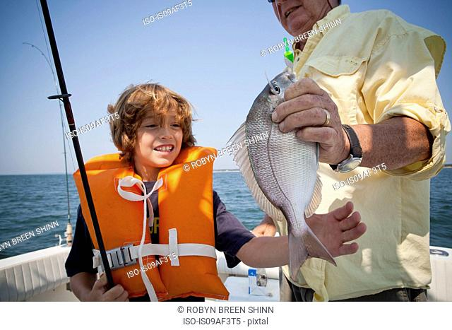 Boy and grandfather with caught fish on boat, Falmouth, Massachusetts, USA