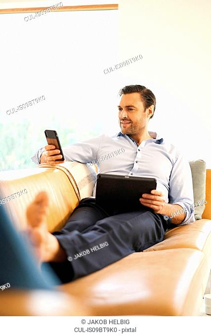 Mature man looking at smartphone whilst reclining on sofa