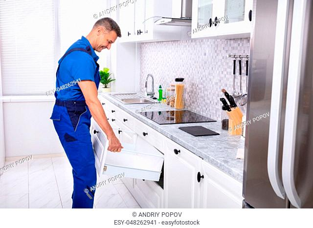 Happy Handyman Fixing Drawer In Cabinet At Home