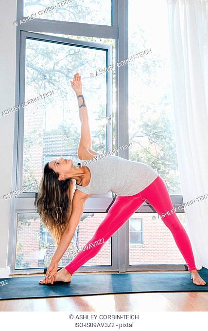 Woman in Triangle pose (Utthita Trikonasana)
