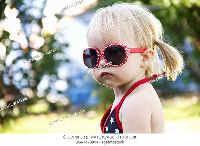 A one year old toddler wearing bright red sunglasses on Independence Day in Liberty Lake, Washington, USA