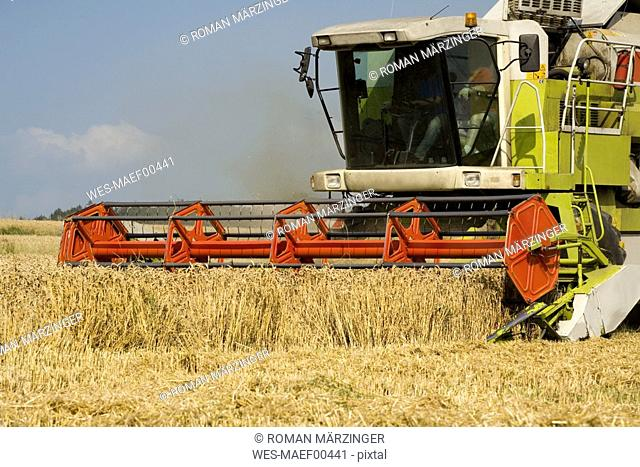 Germany, Bavaria, Combine harvester harvesting wheat