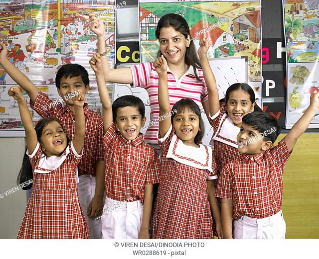 South Asian Indian teacher standing with children raising hands in nursery school MR