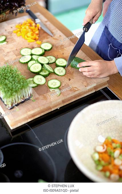 Woman slicing cucumber in kitchen