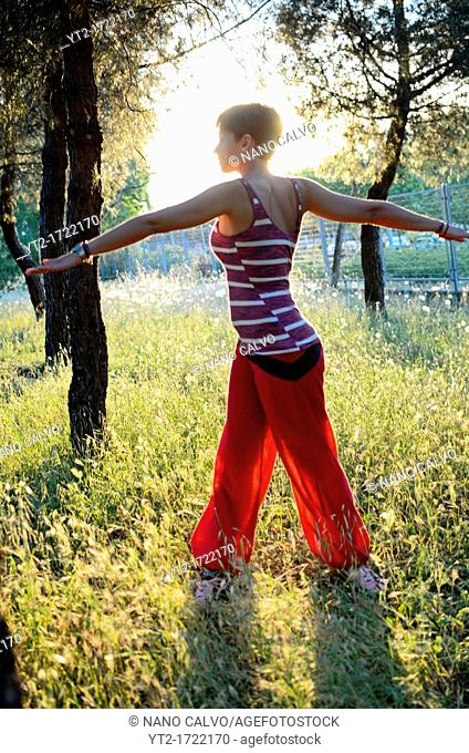 Young woman exercises in nature