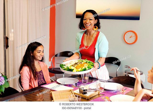 Woman serving gnocchi and broccoli dish