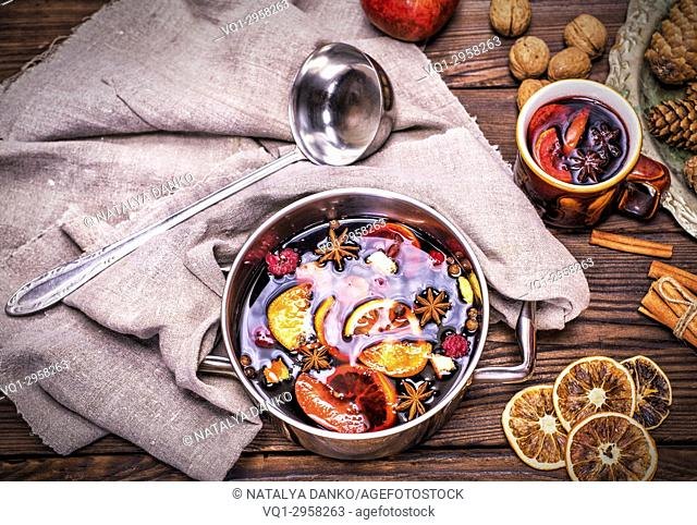 mulled wine in a saucepan on a brown wooden background, top view