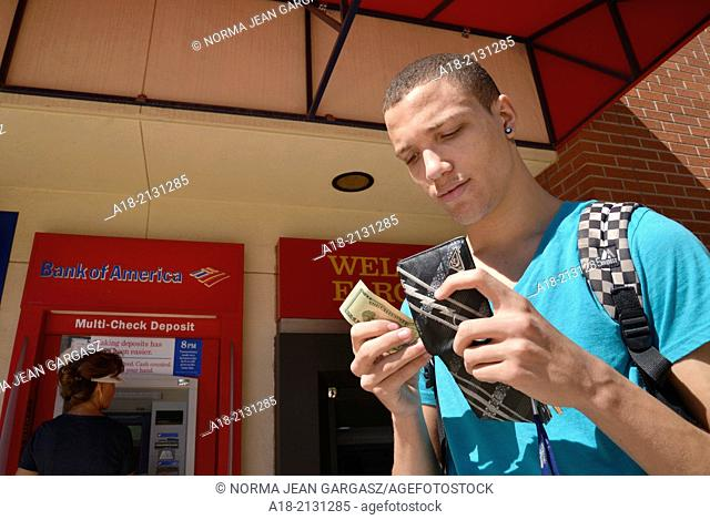 A young man with a wallet and money on a college campus