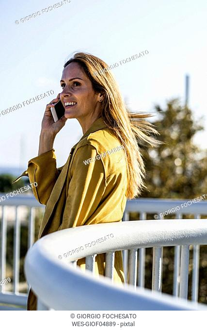 Smiling woman on cell phone on a bridge