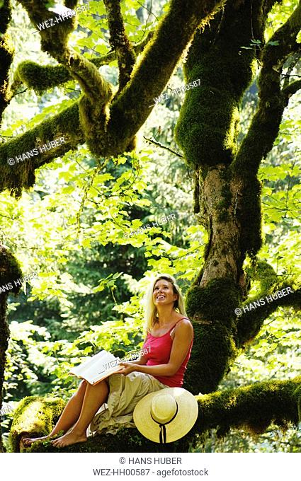Young woman reading in forest