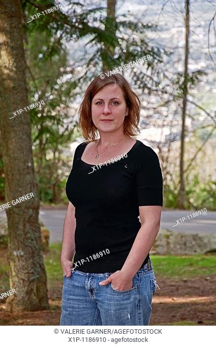 This portrait is a natural looking young Caucasian woman in her twenties wearing a black shirt and blue jeans in a casual outdoor setting Background is...