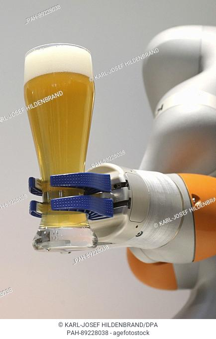 A Kuka robot holds up a glass of beer after pouring it at the 2016 balance sheet press conference of the industrial robot manufacturer held at the Kuka...