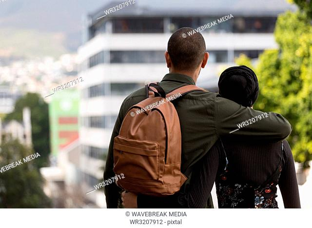 Couple standing with arm around in city