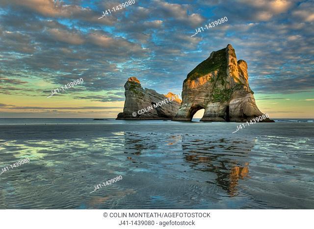 Archway Islands, sunrise lights up high clouds, Wharariki beach, near Collingwood, Golden Bay, New Zealand