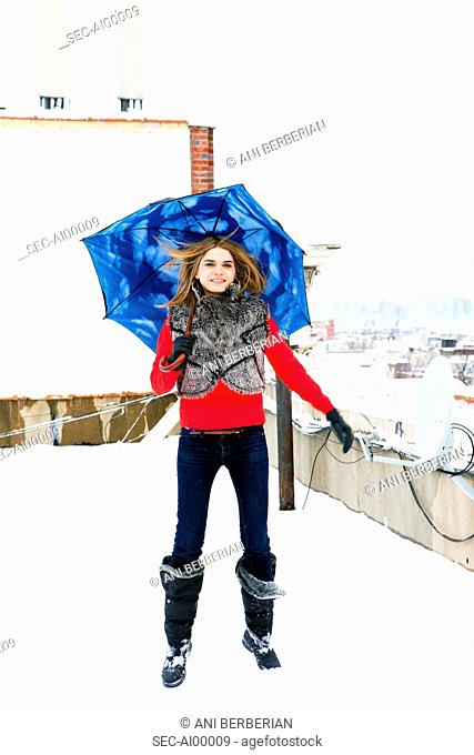 Woman with sky patterned umbrella on snow covered rooftop