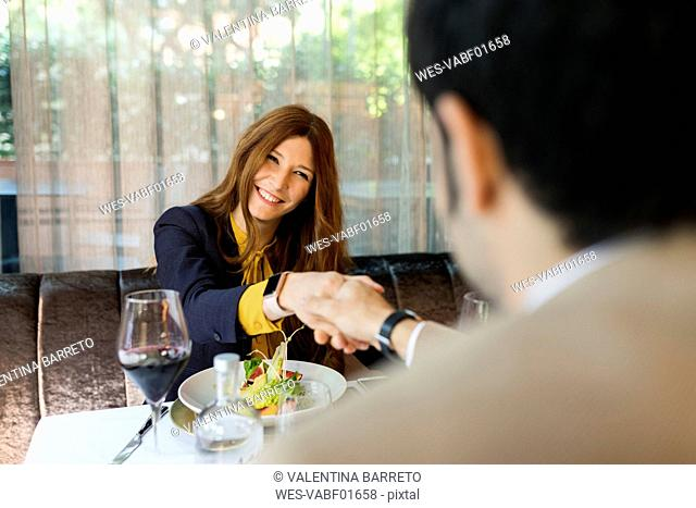 Smiling woman shaking hands with man and in a restaurant
