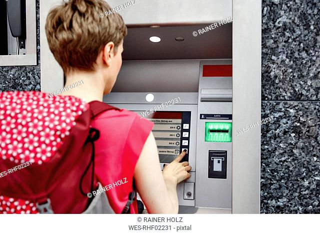Rear view of woman using cash machine