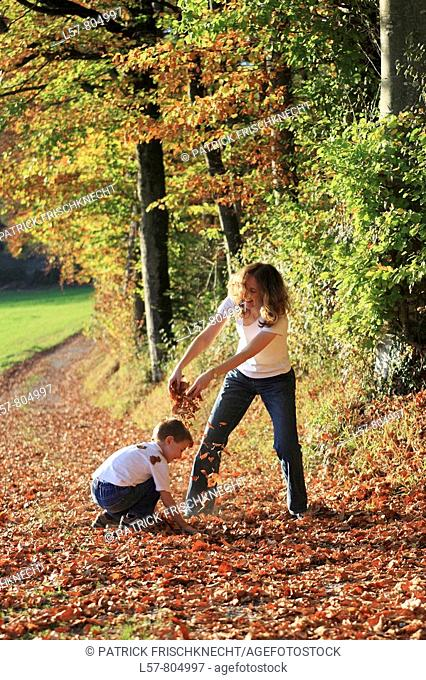 Mother and son playing with leaves in fall, having fun, autumn foliage covering path in forest, autumn, fall, Zuerich, Switzerland