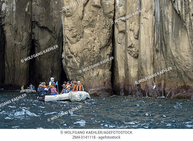 People in zodiacs exploring the coastal cliffs of San Cristobal Island (Isla San Cristobal) or Chatham Island, Galapagos Islands, Ecuador