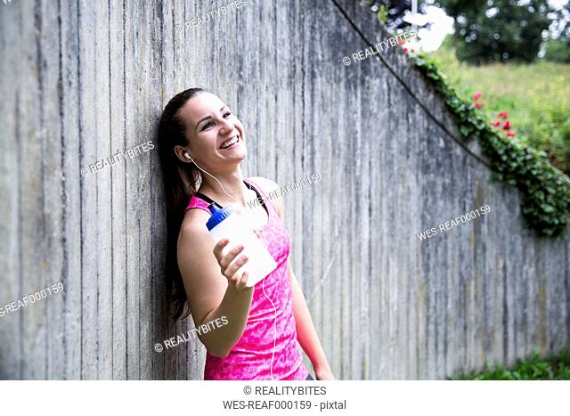 Happy sportive young woman holding drinking bottle