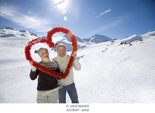 Senior couple holding red heart in mountains on winter day