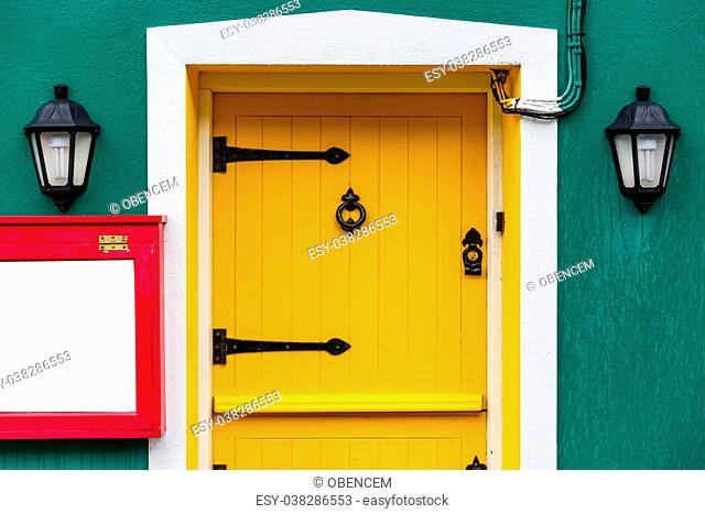 Photo of a yellow front door and two decor lamps