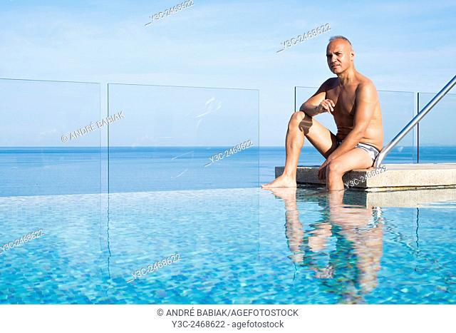 Man, 55 years old, hispanic ethnicity, sitting at upscale infinity swimming pool on the roof top of a condo building in Mexico