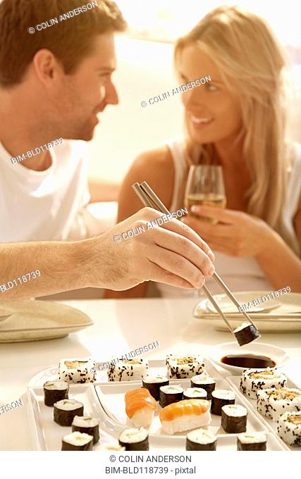 Caucasian couple eating sushi