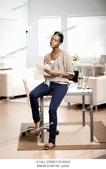 African American woman sitting on desk in home office