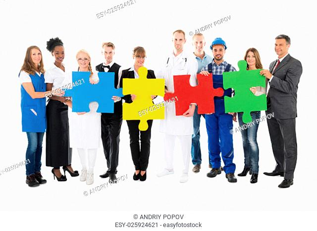 Portrait of confident people with various occupations holding jigsaw pieces while standing against white background