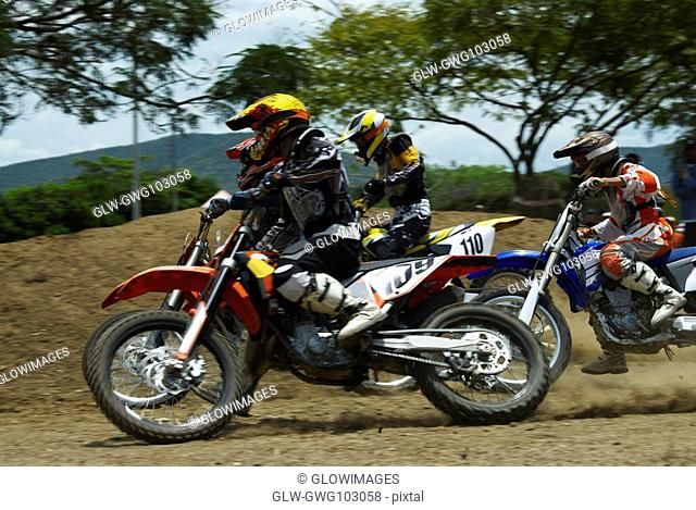 Three motocross riders riding motorcycles on a dirt road