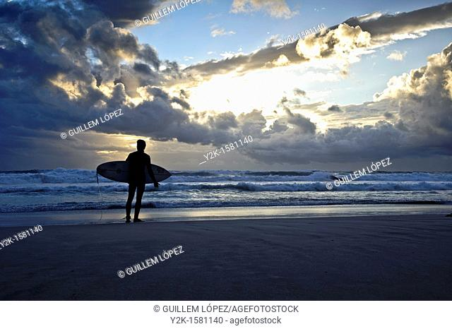 Silhouette of a surfer with his board watching the sea at sunset time, Tarifa, Andalucia, Spain