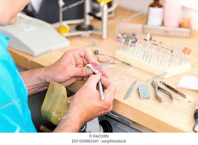 Cropped image of dental technician's hands working on teeth model in workshop