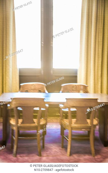 Table and chairs near windows in a library